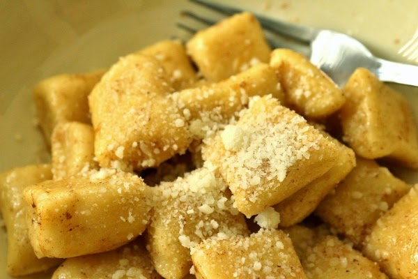 A closeup of dunderi gnocchi in a shallow bowl topped with cheese