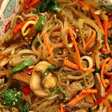 A dish of Korean sweet potato noodles with meat and vegetables (japchae)