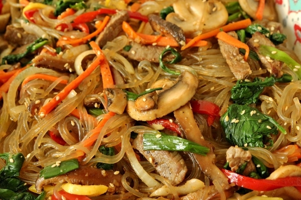 a closeup of sweet potato noodles with colorful vegetables