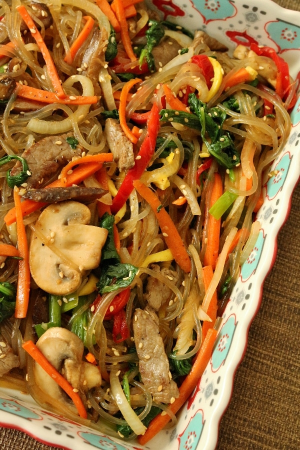 a dish of stir-fried sweet potato noodles with colorful vegetables and strips of beef