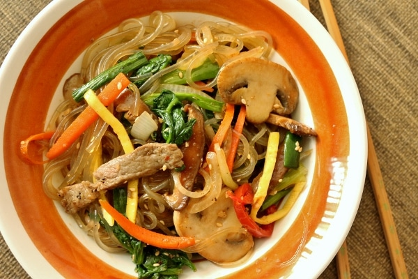 A bowl filled japchae made with sweet potato noodles, beef, and colorful vegetables
