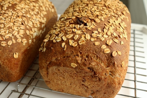 two loaves of whole wheat bread topped with oats on cooling racks