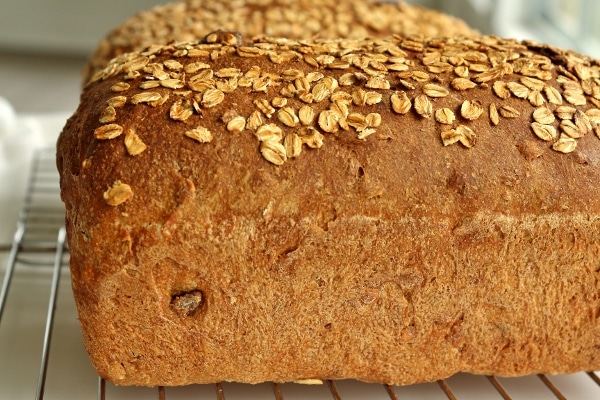 a side view of a loaf of whole wheat sandwich bread topped with oats