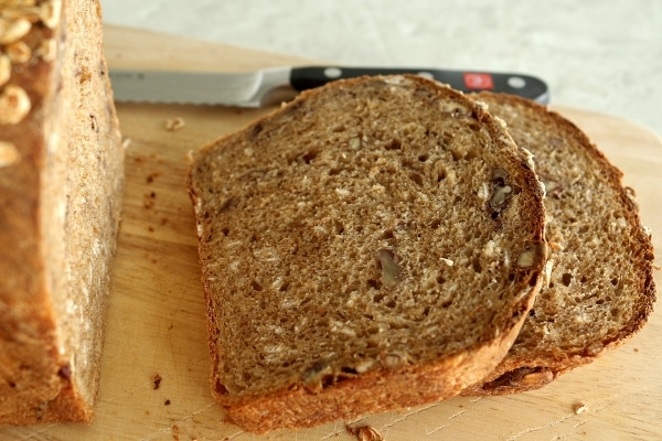 a closeup of slices of whole wheat bread with oats and pecans on a wooden board
