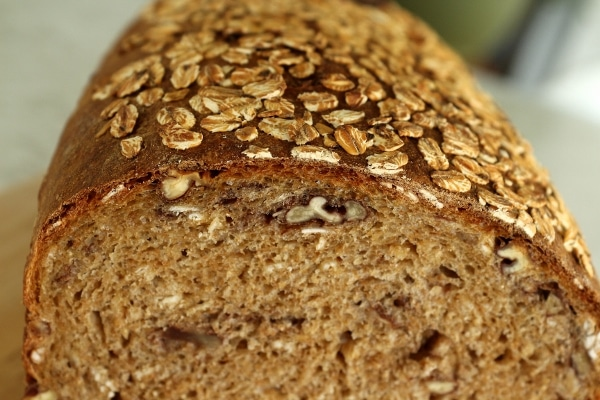 A closeup of a piece whole wheat bread with pecans and oats