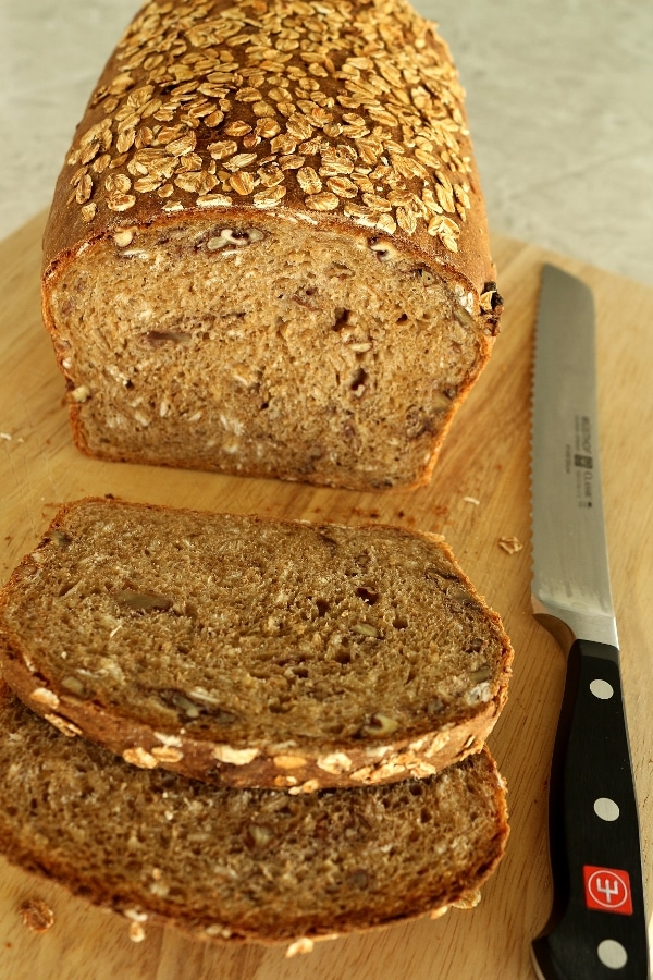 a half-sliced loaf of whole wheat sandwich bread with oats on a wooden board