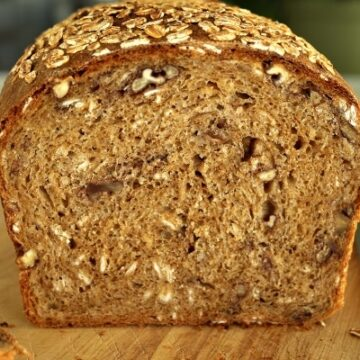 a cross-section of a loaf of whole wheat sandwich bread with oats and pecans