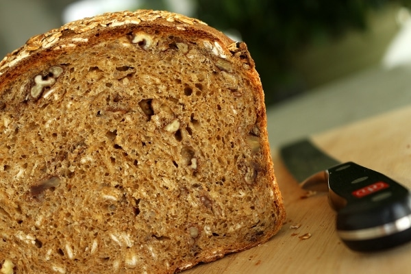 a closeup of a cross-section of whole wheat sandwich bread with oats and pecans