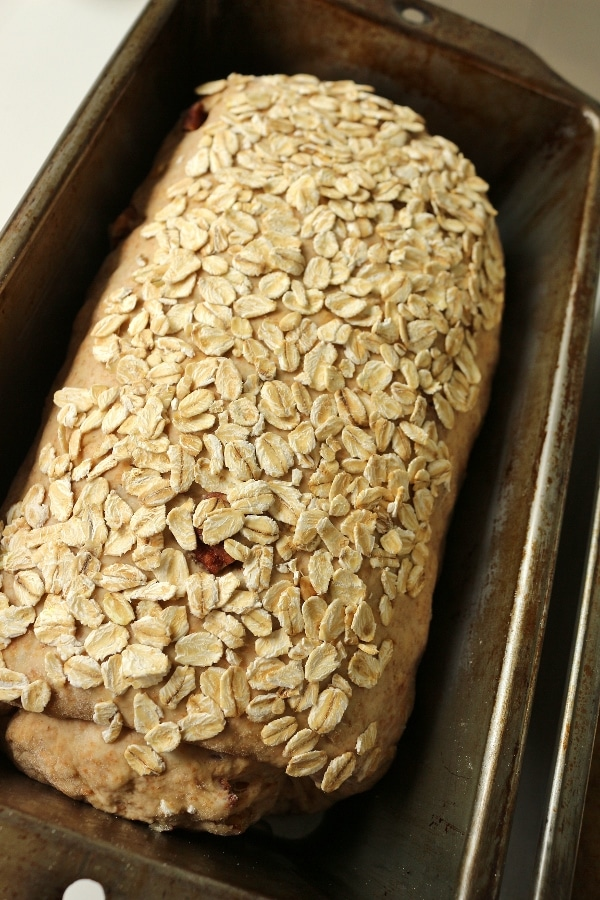 a loaf of unbaked bread topped with oats in a metal pan before proofing