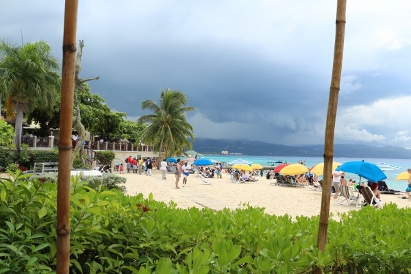dark storm clouds in the distance beyond a tropical beach