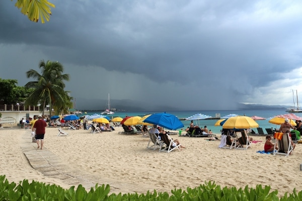 A group of people sitting under beach umbrellas with a gloomy storm in the distance