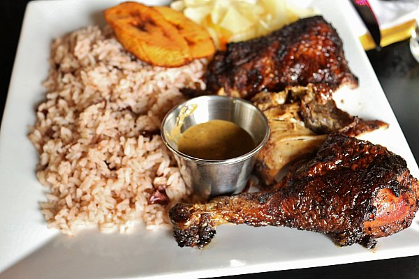 A plate of jerk chicken with rice and peas and plantains