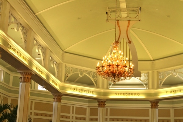 a chandelier hanging from the ceiling in a hotel lobby