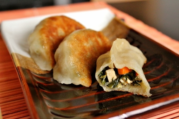 Three pan-fried vegetable dumplings, one with a bite taken out so you can see the filling