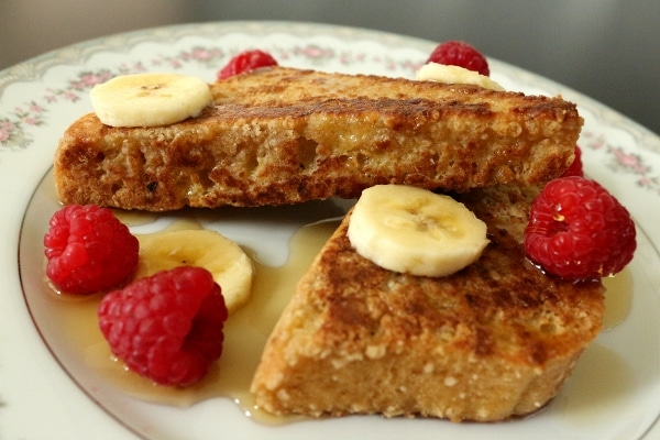 closeup of french toast on a plate with whole raspberries and sliced banana