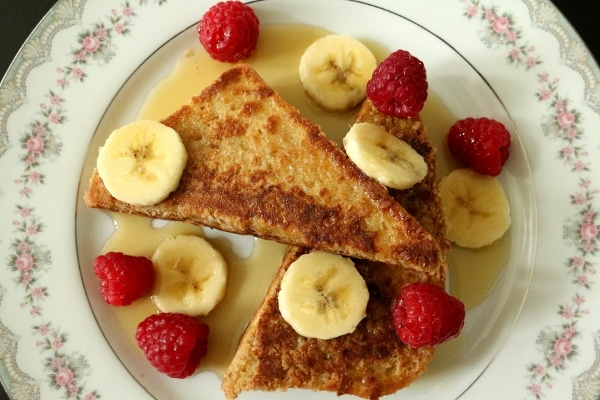 overhead view of french toast with sliced bananas and raspberries