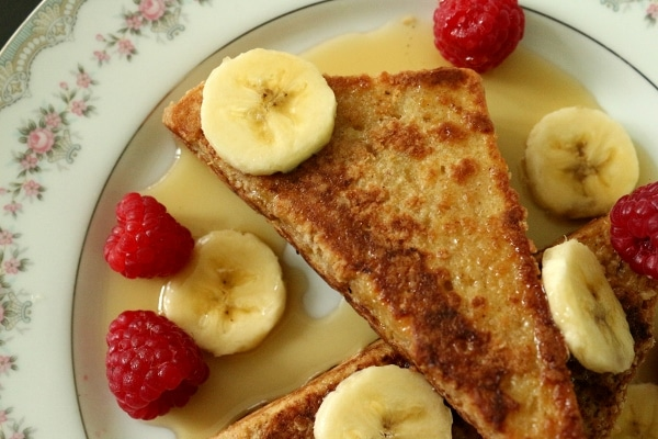 overhead closeup of french toast on a plate with sliced bananas and raspberries