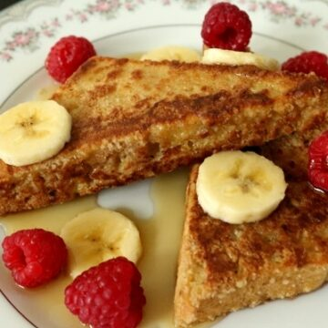 two triangles of french toast on a plate with raspberries and bananas