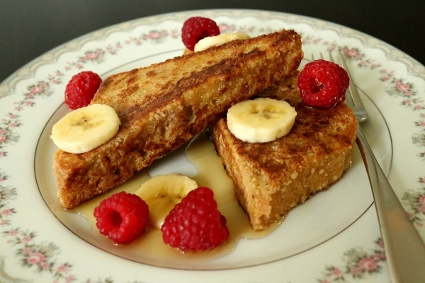 two pieces of french toast on a plate with syrup, sliced bananas, and raspberries