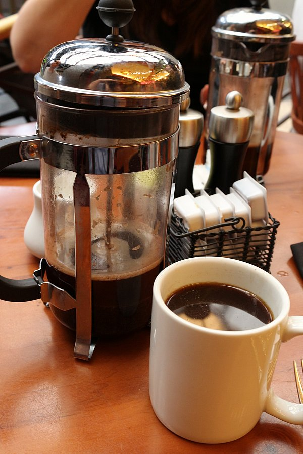 a French press and a cup of coffee on a table
