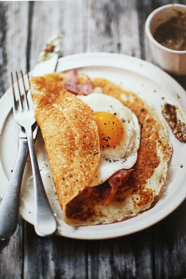 a crepe filled with ham and egg on a plate