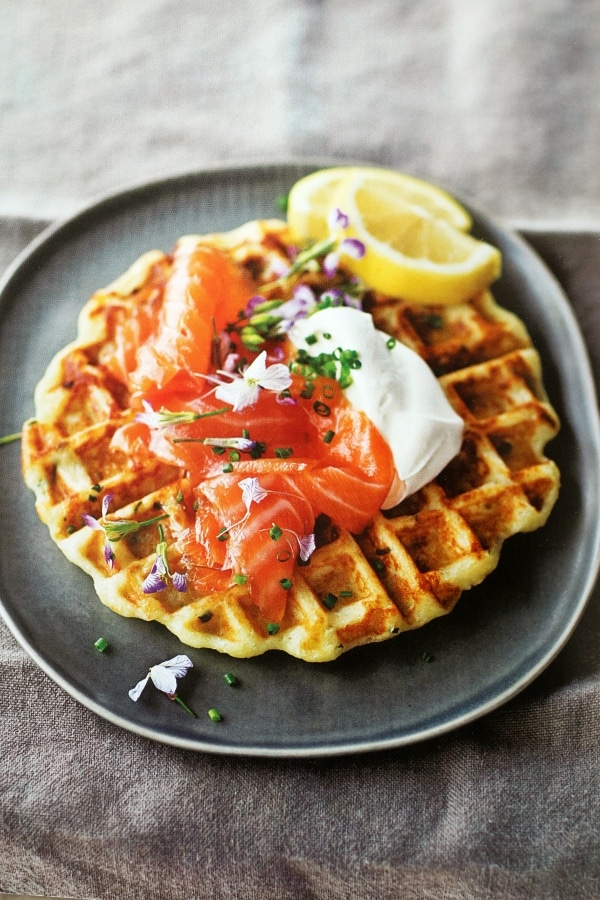 a large waffle on a plate topped with sour cream and cured salmon