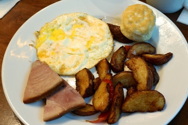 A plate of egg, breakfast potatoes, ham, and a small biscuit