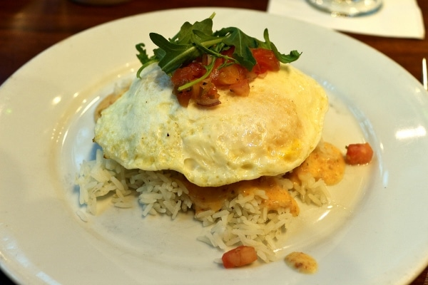 A plate of rice topped with a fried egg and chopped tomatoes