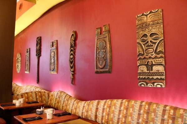 Polynesian themed wall hangings over a banquette bench