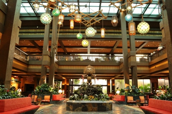 the lobby of Disney\'s Polynesian Village Resort with a tiki statue and colorful hanging lights