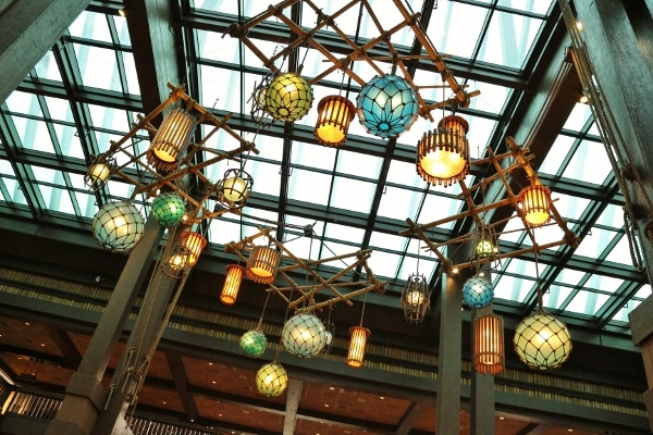 a view looking up at brightly colored hanging lights and glass skylights over the Polynesian lobby