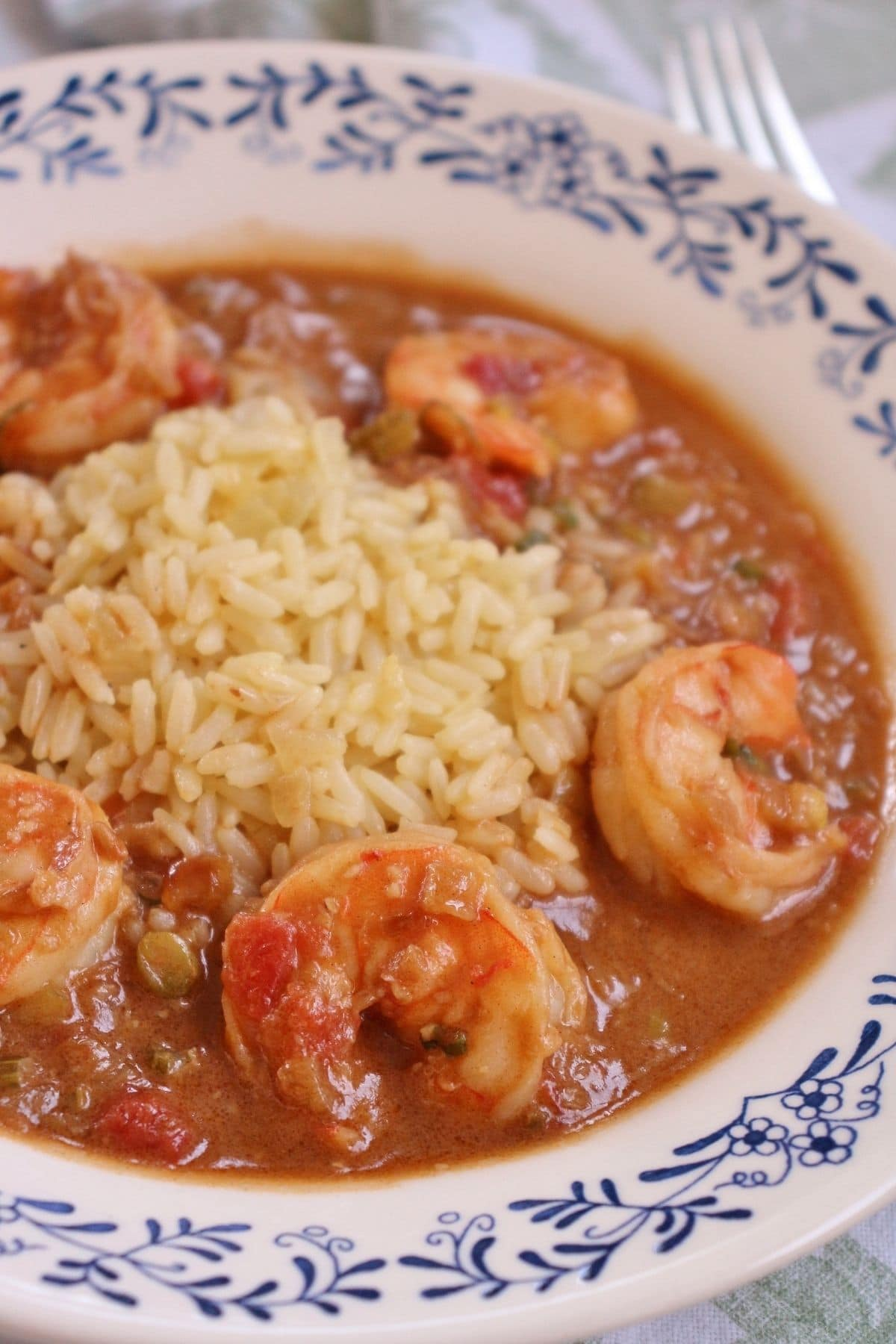 side closeup of a shallow white and blue bowl filled with rice and shrimp etouffee