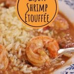 closeup of a fork scooping up shrimp etouffee and rice from a shallow bowl