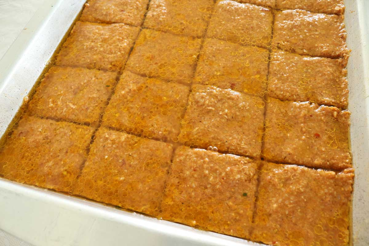 A tray of kofte cut into squares, topped with water and oil, and ready to bake.