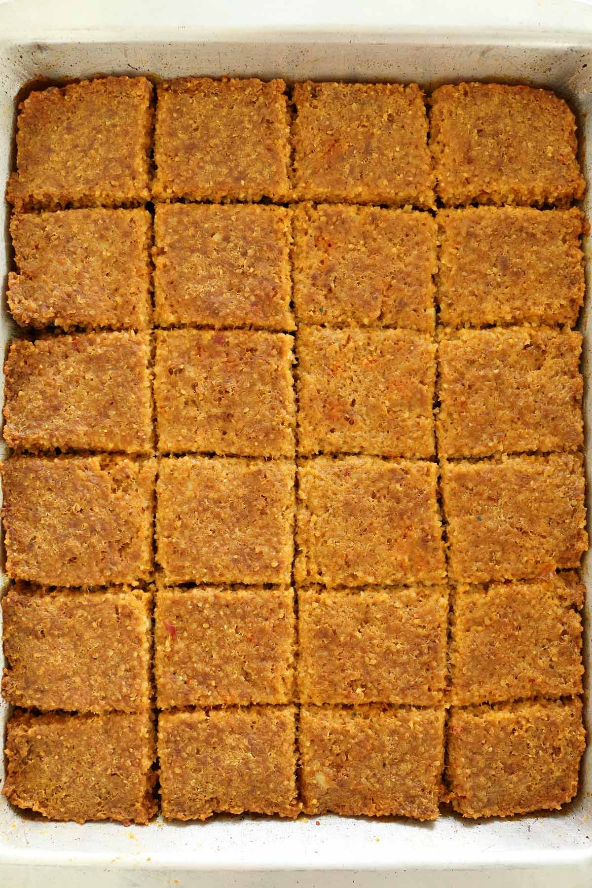 A pan of baked sini kofte cut into squares.
