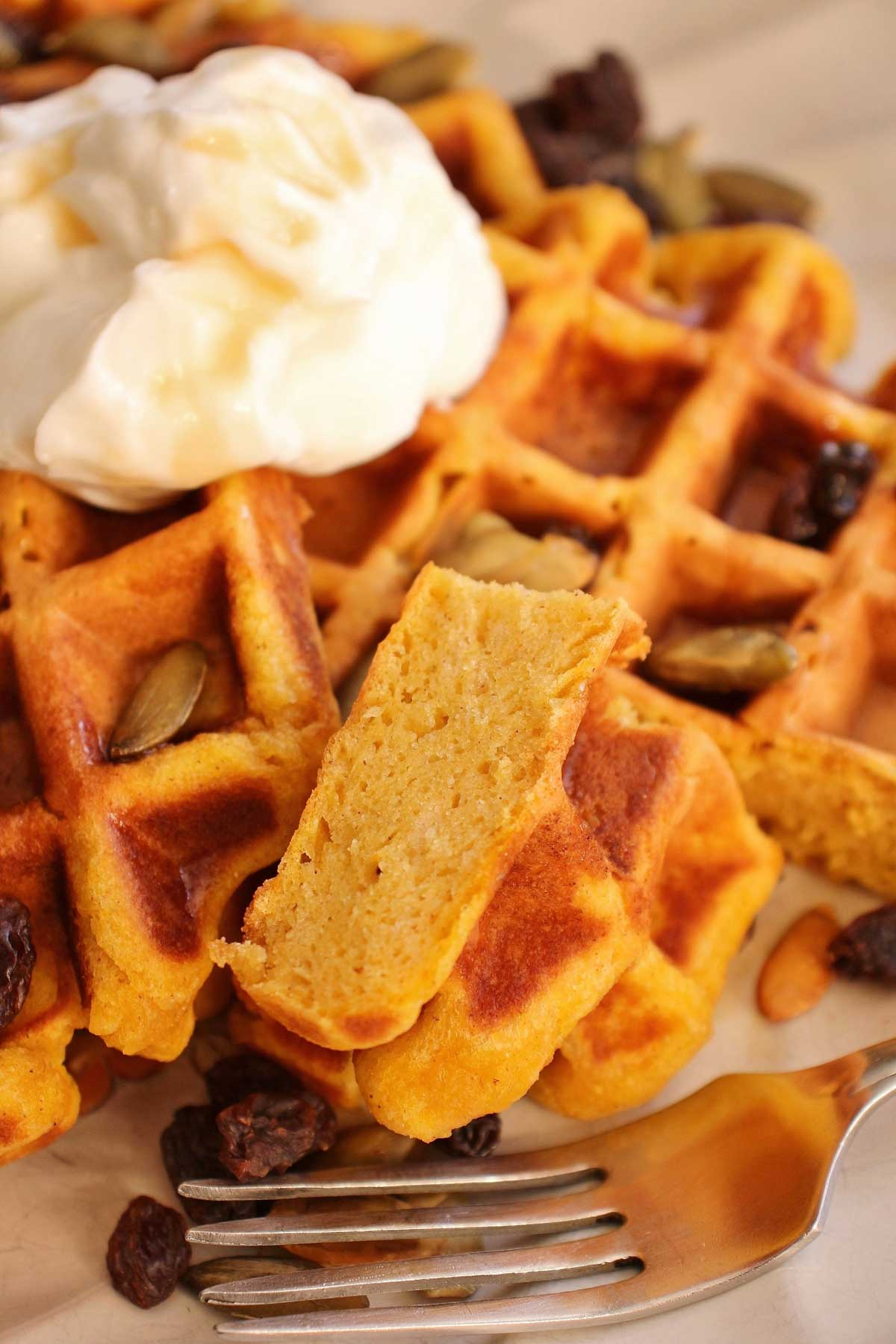 Closeup of a piece of pumpkin waffle on a plate showing off the tender interior.