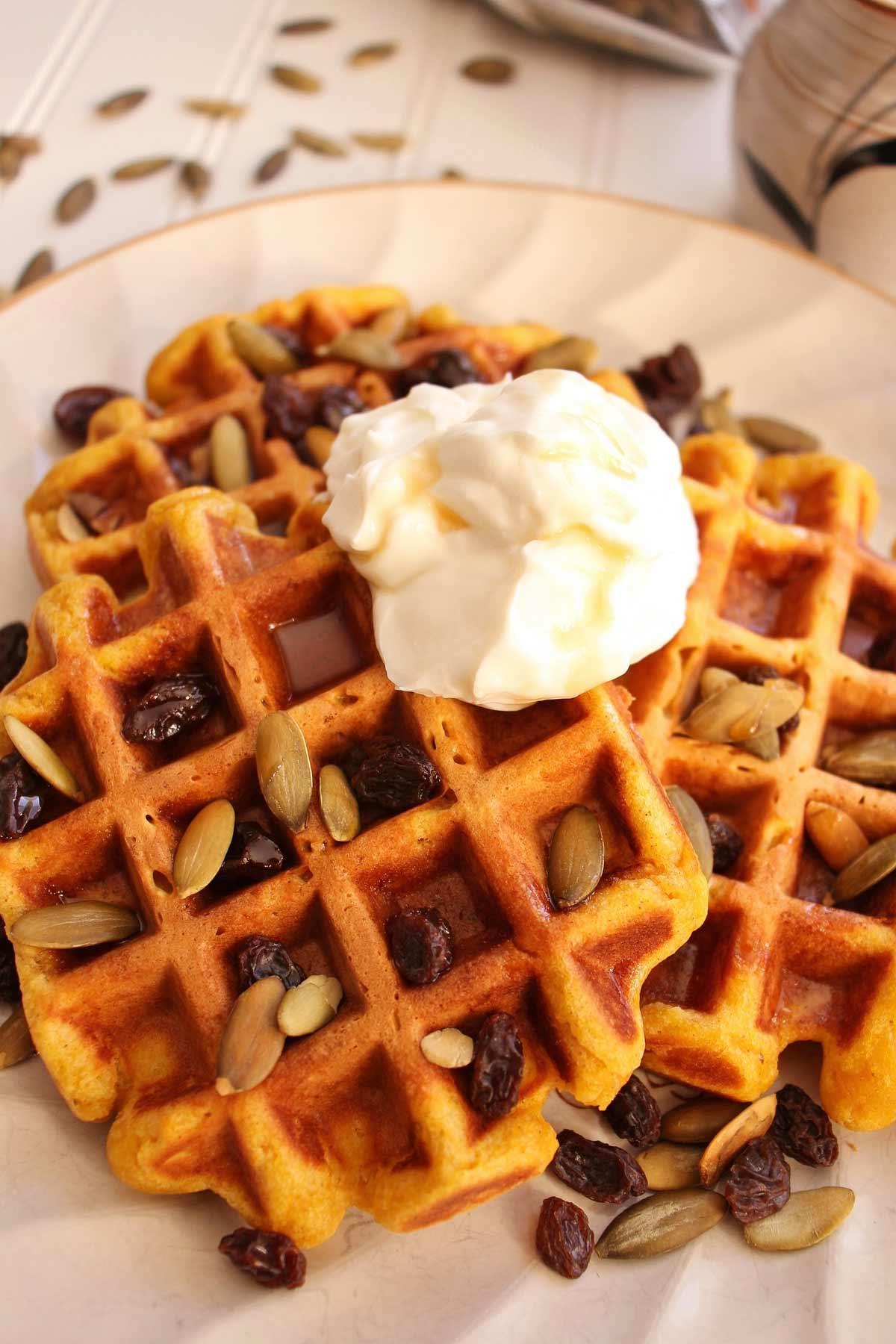Closeup of rectangular pumpkin waffles topped with sour cream, pepitas, and raisins.