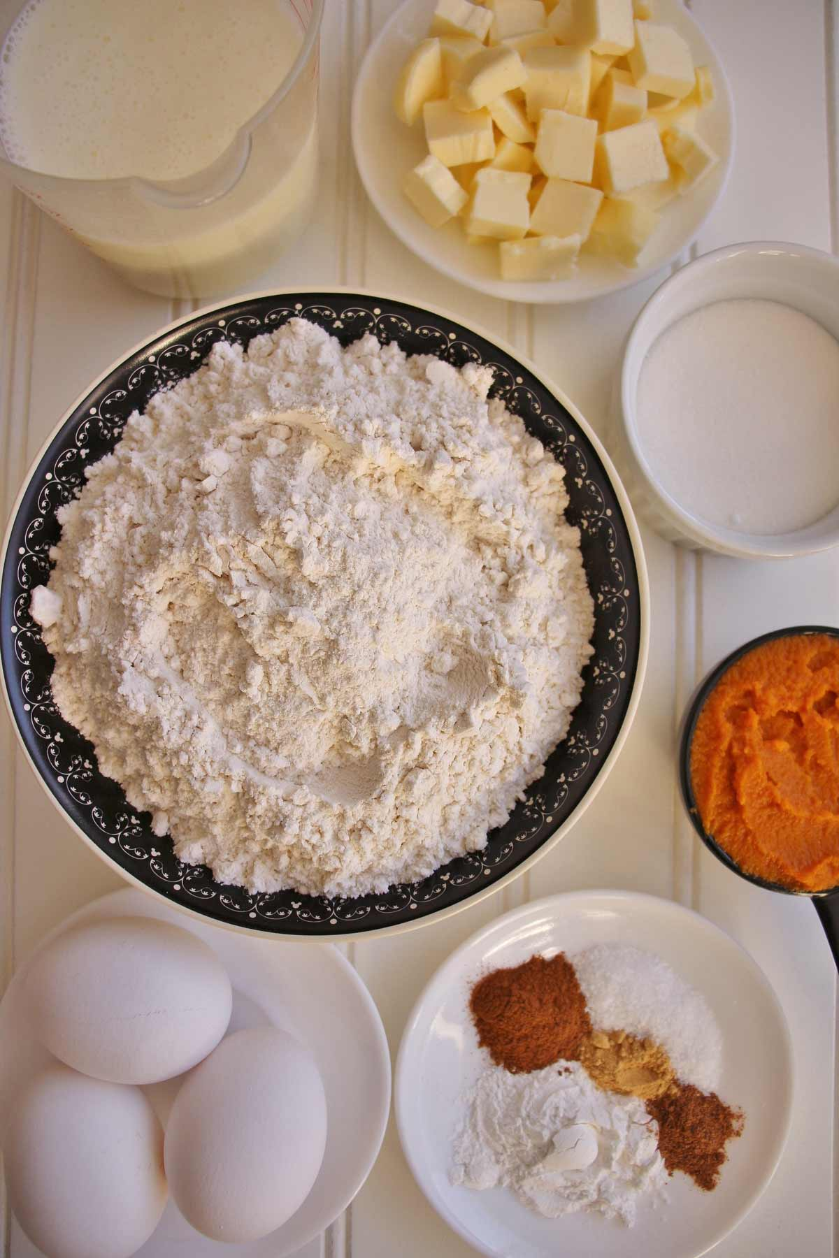 Buttermilk, cubed butter, flour, sugar, pumpkin puree, eggs, and spices on a white surface.