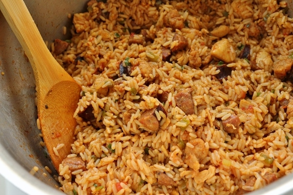 chicken and andouille jambalaya in a large pot with a wooden spoon