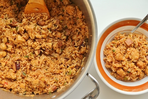 a pot of chicken and andouille sausage jambalaya with a bowl of jambalaya on the side