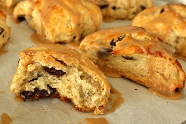 a tray of chocolate chip scones with one half-eaten scone