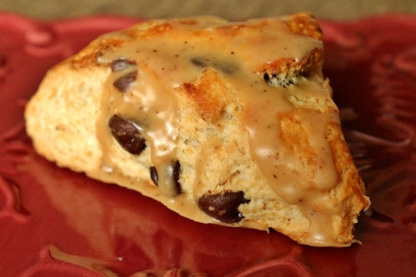 A close up of a chocolate chip scone with espresso glaze on a red plate