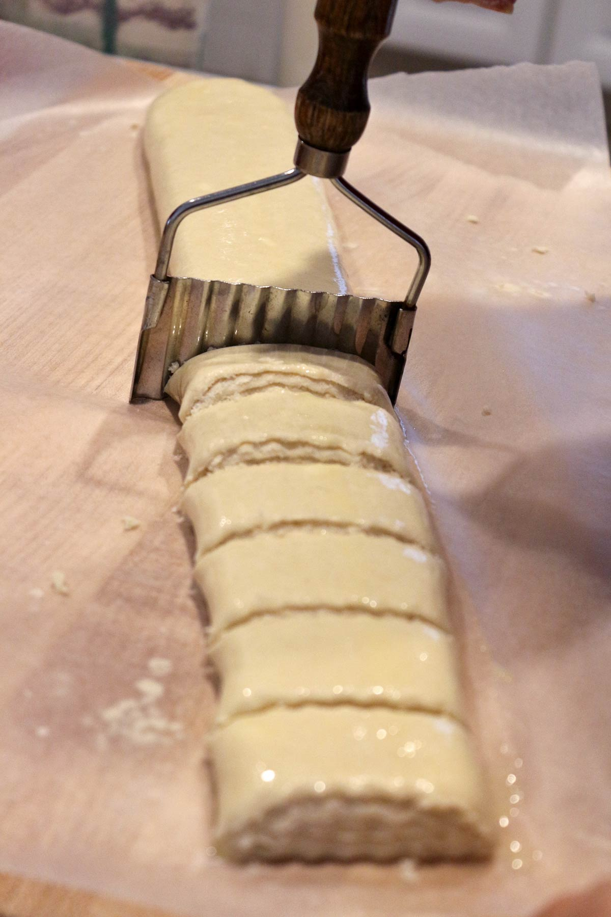 Cutting the gata roulade into individual pieces with a serrated vegetable cutter.