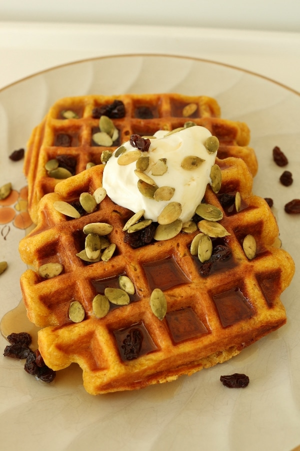 two pumpkin waffles with raisins, sour cream and pumpkin seeds on a plate