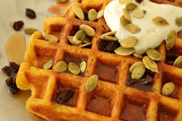 A closeup of pumpkin waffles with pumpkin seeds and raisins on top
