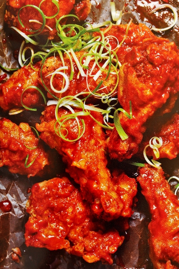 a photo from a cookbook of Korean fried chicken garnished with scallions