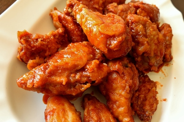 closeup of Korean fried chicken in spicy red sauce