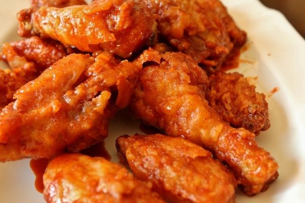 a closeup of crispy Korean fried chicken on a white platter