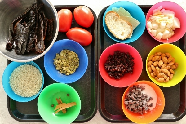 colorful bowls filled with various ingredients for mole sauce