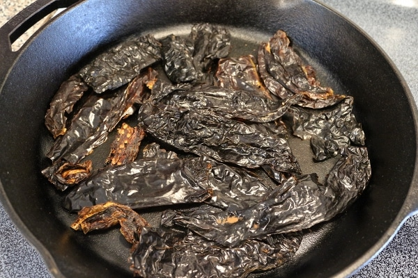 dried chiles toasting in a cast iron pan